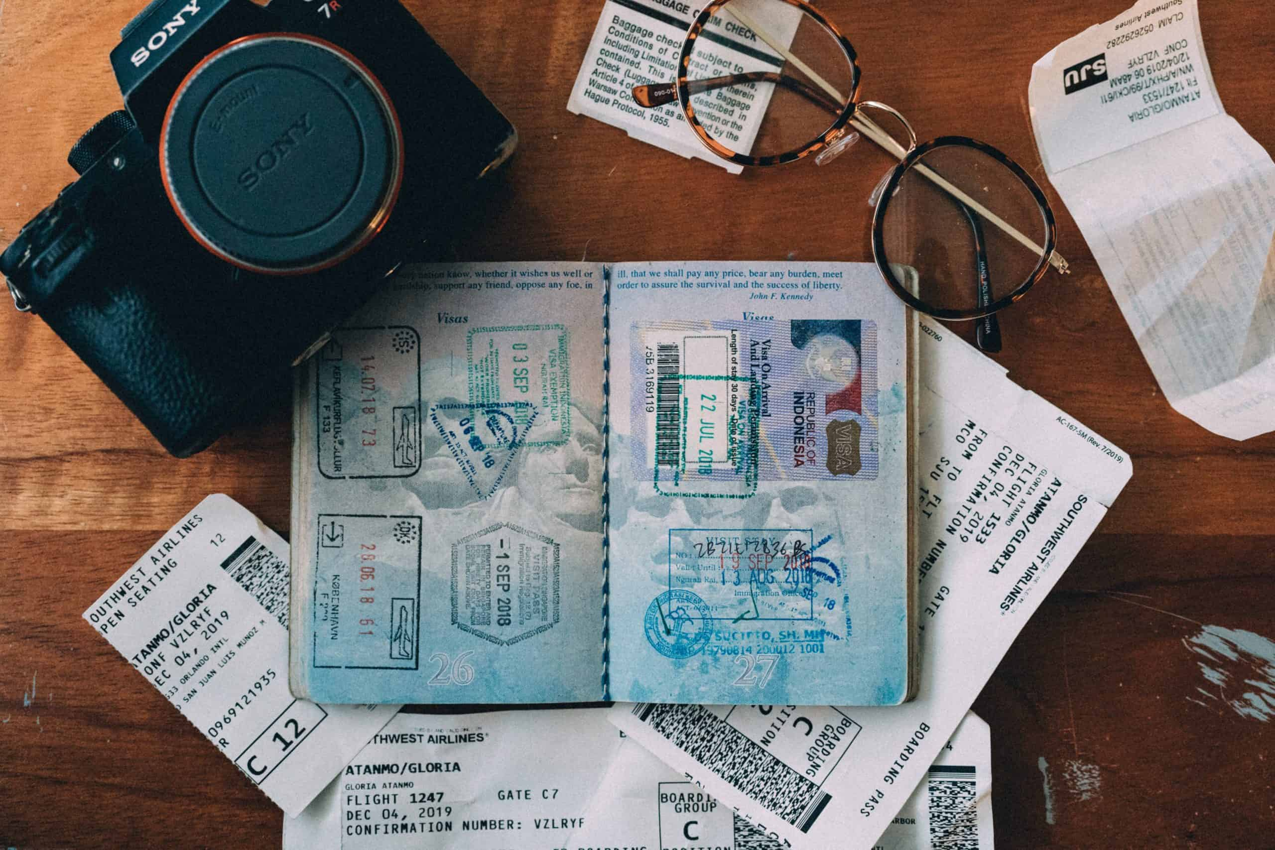 passport, camera and travel documents on a desk