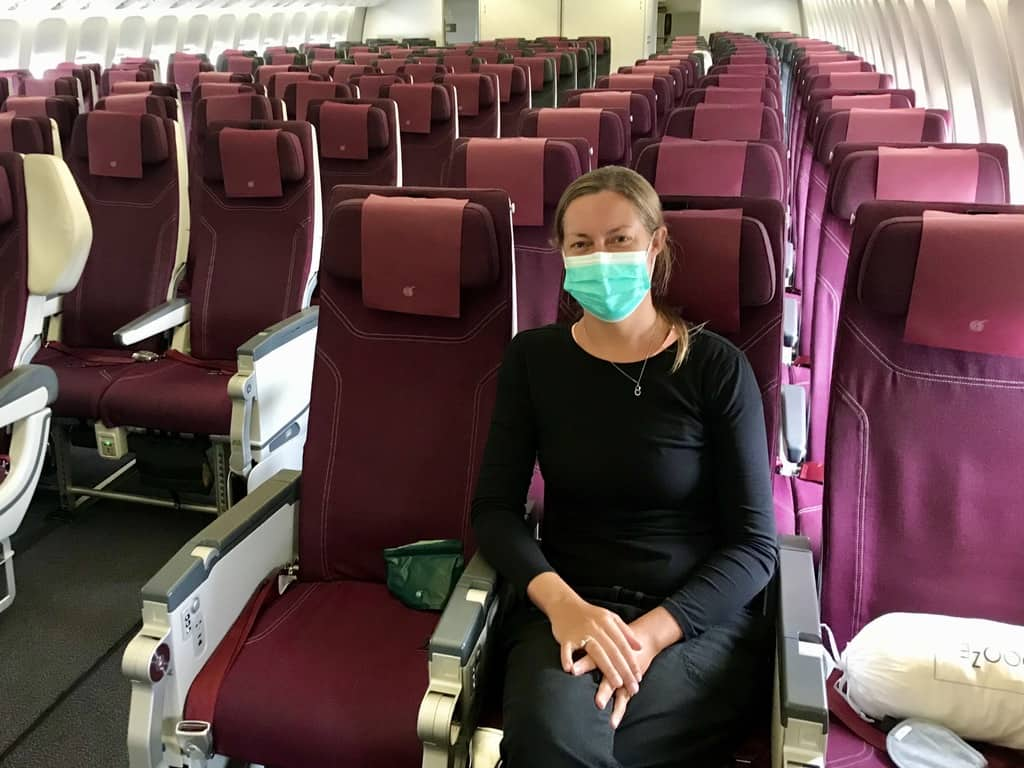 Joannda on the plane during the pandemic wearing a facemask